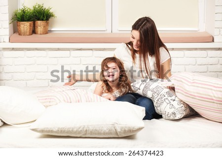 young sexy mother spending daytime, having fun with her daughter, lying on the bad with pillows in light room