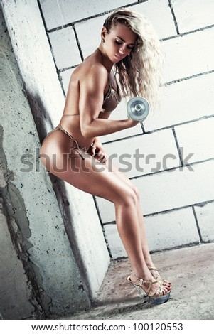 Young sexy muscular woman with dumbbell.
