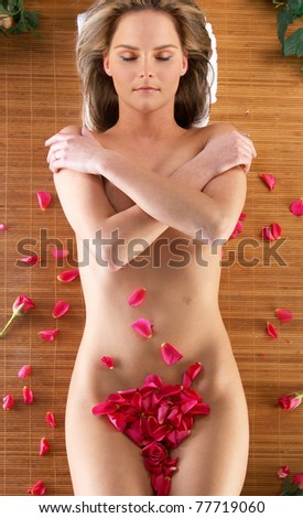 Young sexy naked woman with some petals over belly - stock photo