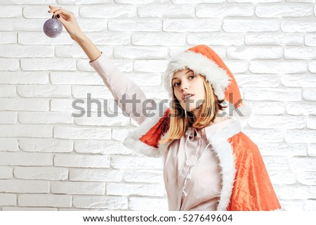 young sexy new year woman or cute girl with pretty face in red christmas santa claus holiday hat and coat holds silver decorative ball on white brick wall background, copy space