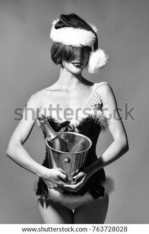 young sexy new year woman or girl with and red lips on pretty face in christmas santa claus hat and holiday costume holds metallic pail with wine or champagne bottle in studio on grey background