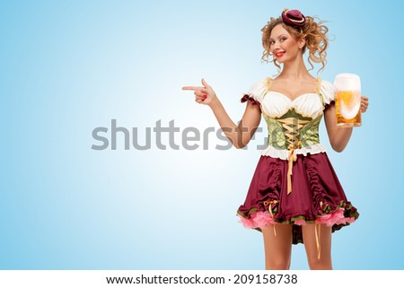 Young sexy Oktoberfest waitress wearing a traditional Bavarian dress dirndl holding a beer mug, and pointing aside on blue background.