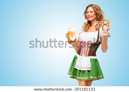 Young sexy Oktoberfest waitress wearing a traditional Bavarian dress dirndl offering a pretzel and beer mug on blue background.