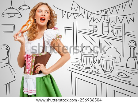 Young sexy Oktoberfest woman wearing a traditional Bavarian dress dirndl eating a pretzel on sketchy bar counter background. - stock photo