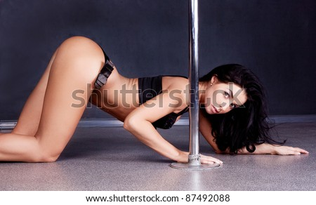 Young sexy pole dance woman against dark background