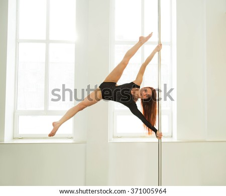 Young sexy pole dance woman. Bright white colors. - stock photo