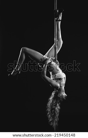 Young sexy pole dance woman. Contrast black and white colors. - stock photo