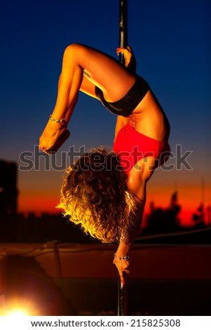 Young sexy pole dance woman on city background. - stock photo