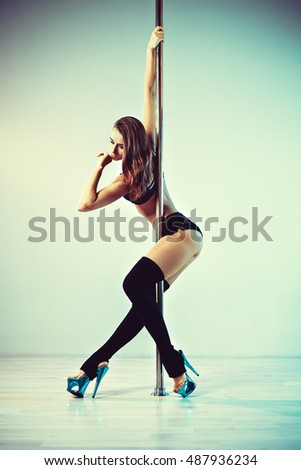 Young sexy pole dance woman. Vintage film style colors.