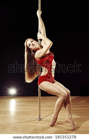 Young sexy pole dance woman with fluttering hair performing on stage - stock photo
