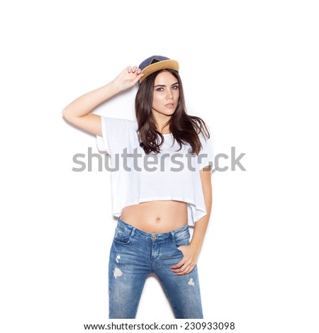 Young sexy skater girl. Indoor fashion portrait of young beautiful woman in t-shirt, jeans and cap. White background, not isolated - stock photo