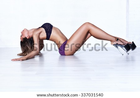 Young sexy slim woman dancer in lingerie stretching on white wall background - stock photo