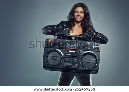 Young sexy smiling brunette woman in black leather jacket holding big old boom box. - stock photo