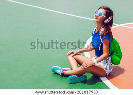 Young sexy sportive tan woman siting in fashion sportive outfit, neon backpack and mirrored sunglasses and listening her favorite music in earphones and enjoy summer hot day. - stock photo