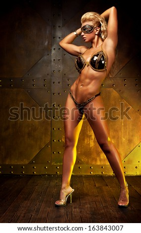 Young sexy sports woman on wall background.