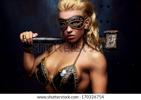 Young sexy strong woman with hammer.