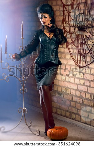 Young sexy witch dressed in vintage dress - stock photo