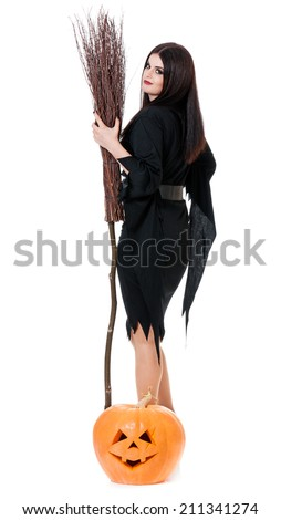 Young sexy witch with broom and pumpkin over white background