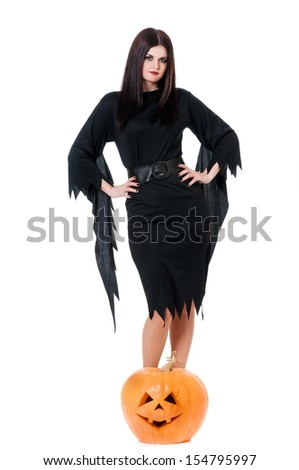 Young sexy witch with halloween pumpkin over white background