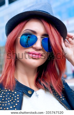 Young sexy woman closeup portrait. Stylish woman posing on the street with interested look,wearing bike leather coat,grey hat and blue mirrored sunglasses - stock photo