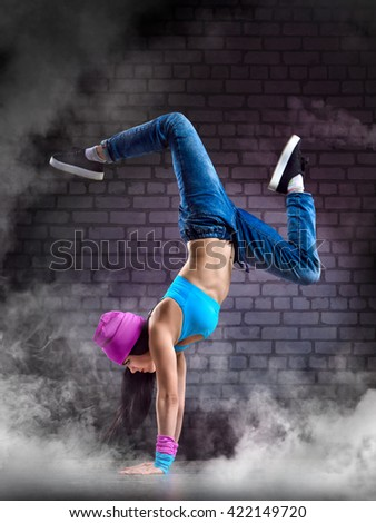 Young sexy woman dancer dancing on wall background