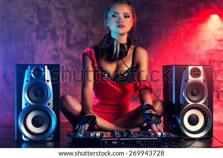 Young sexy woman dj playing music. Big loud speakers, headphones and dj mixer on floor. - stock photo