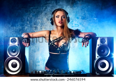 Young sexy woman dj playing music. Big loud speakers, headphones and dj mixer on table. - stock photo