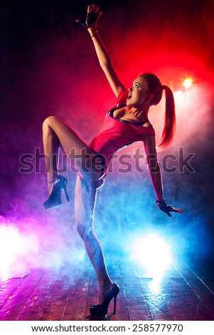 Young sexy woman go-go dancer in club. Red and blue lights with smoke effect. - stock photo