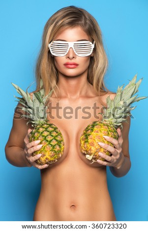 Young sexy woman happy smiling only in glasses posing on blue background with pineapple who cover her breast - stock photo
