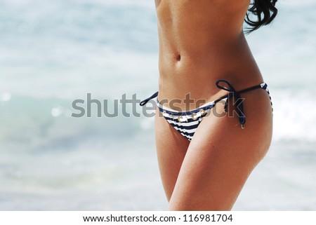 Young sexy woman in bikini on sea background - stock photo