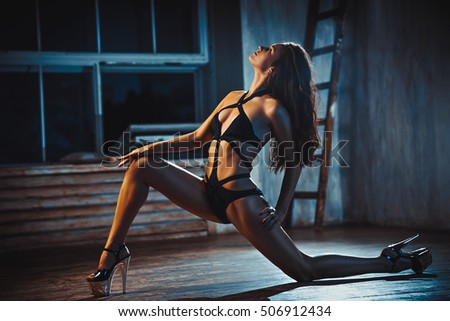 Young sexy woman in black lingerie in dark night interior