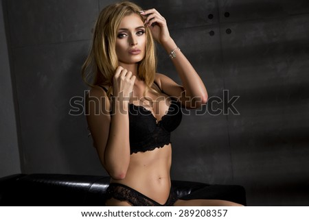 Young sexy woman in black lingerie in dark room