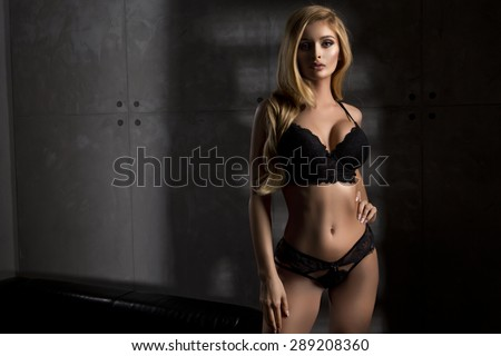 Young sexy woman in black lingerie in dark room - stock photo