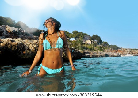 young sexy woman in blue bikini at the beach having a bath in the sea by the rocks enjoying summer holidays in Spain coast with wet tan body in relax and freedom concept - stock photo