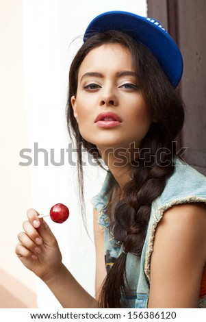 Young sexy woman in blue cap and jeans jacket  holding lollipop looking at camera.  Outdoors, lifestyle. - stock photo
