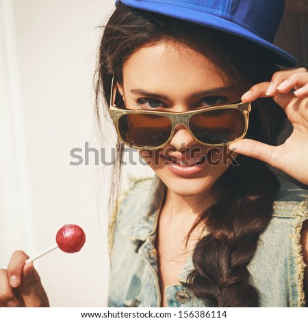 Young sexy woman in blue cap and jeans jacket  looking at camera  through sunglasses .  Outdoors, lifestyle. - stock photo