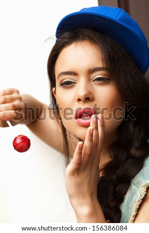 Young sexy woman in blue cap  holding lollipop.  Outdoors, lifestyle. - stock photo