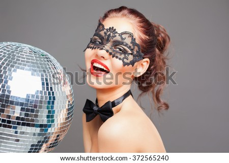 Young sexy woman in carnival mask keeping disco ball. Party. Fashion. Venetian carnival. - stock photo