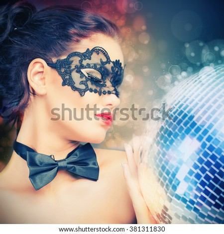 Young sexy woman in carnival mask keeping disco ball. Party. Night club. Fashion. Venetian carnival. - stock photo