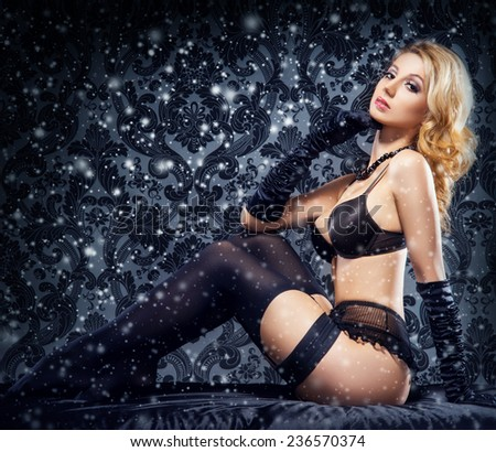 Young sexy woman in erotic lingerie over snowy Christmas background  - stock photo