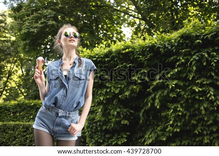 Young sexy woman in jeans outfit looking and mirror sunglasses eating ice cream. Hipster girl. Outdoors, lifestyle. - stock photo