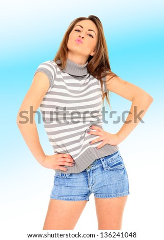 Young sexy woman in jeans shorts over light blue background - stock photo