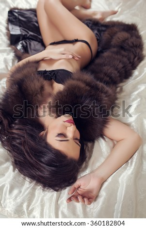 Young sexy woman in lingerie laying in the bed - stock photo