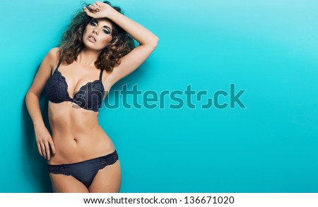 young sexy woman in lingerie posing on blue background - stock photo