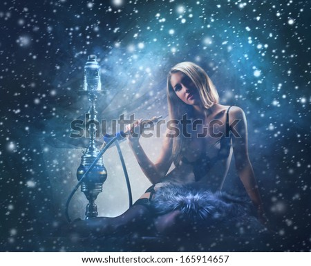 Young sexy woman in luxury underwear smoking the hookah over the Christmas background