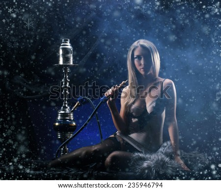 Young sexy woman in luxury underwear smoking the hookah over the Christmas background - stock photo