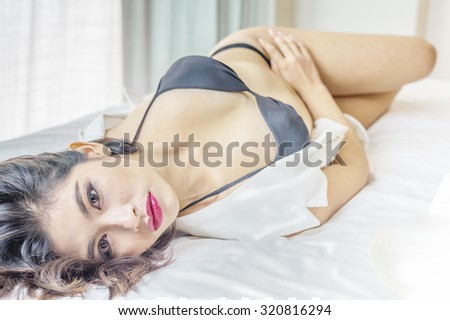 Young sexy woman in sexy black lingerie lying on bed - stock photo