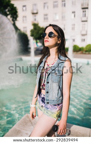 Young sexy woman in sunglasses and jeans jacket . Outdoors, lifestyle.