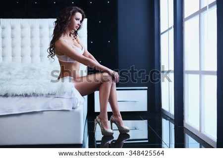 Young sexy woman in white lingerie sitting on bed and looking to window - stock photo