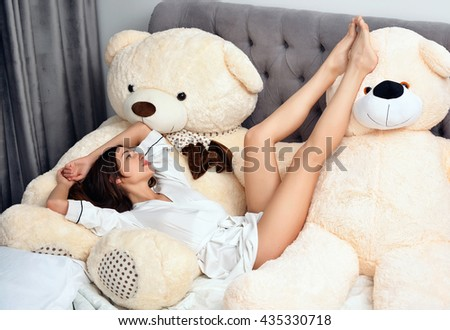 Young sexy woman in white shirt lying in the bed with two toy bears